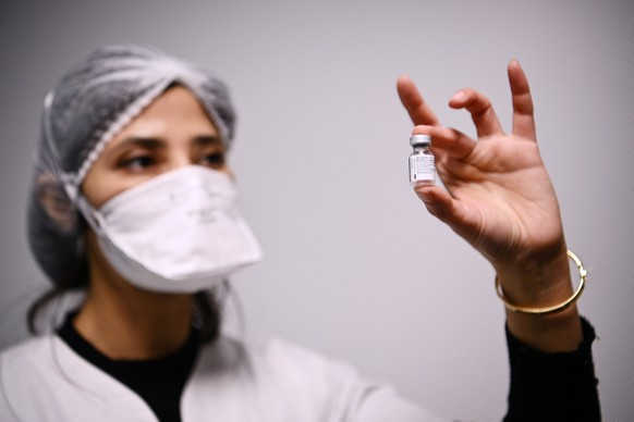 epa08922731 A health worker holds a vial containing the Pfizer-BioNTech COVID-19 vaccine in Aulnay-sous-Bois, France, 06 January 2021, as several French medical representatives and personalities receive the vaccine. France began its coronavirus disease (COVID-19) vaccination campaign on 27 December 2020. The French government has faced criticism over the slow progress of its drive to vaccinate people, a problem compounded by the high levels of public skepticism about the campaign.  EPA/CHRISTOPHE ARCHAMBAULT / POOL  MAXPPP OUT