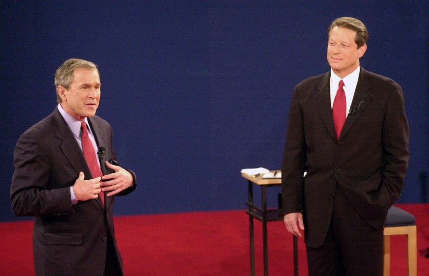 FILE - In this Oct. 17, 2000 file photo, Republican presidential candidate, Texas Gov. George W. Bush, left, speaks as Democratic presidential candidate Vice President Al Gore watches during their third and final debate at Washington University in St. Louis.