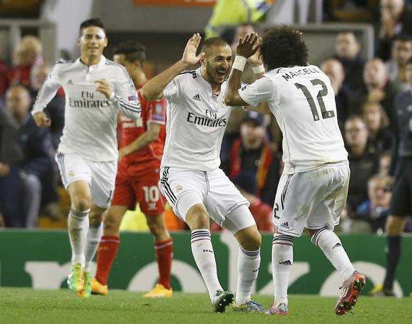 Real Madrid's Karim Benzema (C) celebrates after scoring the second goal with Real Madrid's Marcelo (R) during their Champions League Group B soccer match against Liverpool at Anfield in Liverpool, northern England October 22, 2014.      REUTERS/Phil Noble (BRITAIN  - Tags: SOCCER SPORT)
