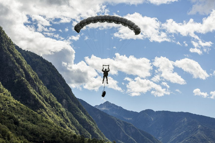 A parascout glides toward the ground, pictured near Locarno in the canton of Ticino, Switzerland, on October 4, 2013. The parascouts of the Swiss Armed Forces are stationed at the military airbase Locarno. Within the frame of their parachute jumping service, the parascouts jump out of a Pilatus Porter PC-6 aircraft, in which there is space for 5-6 parascouts with their baggage. After jumping, the parascouts must open their parachutes as soon as possible in order to get as close as possible to their destination unnoticedly from far away. This is why most jumps are performed at night. (KEYSTONE/Gaetan Bally)  Ein Fallschirmaufklaerer gleitet Richtung Boden, aufgenommen am 4. Oktober 2013 in der Naehe von Locarno. Die Basis der Fallschirmaufklaerer ist der Militaerflugplatz Locarno im Tessin. Die Fallschirmaufklaerer der Schweizer Armee springen beim Sprungdienst aus einem Pilatus Porter PC-6-Flugzeug, in welchem 5-6 Fallschirmaufklaerer mit ihrem Gepaeck Platz finden. Nach dem Sprung muessen sie den Fallschirm so schnell wie moeglich oeffnen, um von weit weg unbemerkt so nah wie moeglich an ein Ziel zu gelangen. Die meisten Spruenge werden deshalb in der Nacht durchgefuehrt. (KEYSTONE/Gaetan Bally)