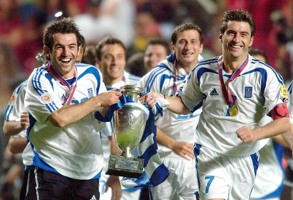 FILE - In this Sunday, July 4, 2004 file photo Georgios Karagounis, left, and Theodoros Zagorakis of Greece run with the trophy after their team's 1-0 victory over Portugal in the Euro 2004 soccer championship final at the Luz stadium in Lisbon, Portugal. English soccer club Leicester City's achievement of winning the Premier League has drawn comparisons with other upsets in sporting history including Greece's victory at Euro 2004. (AP Photo/Dusan Vranic, File)