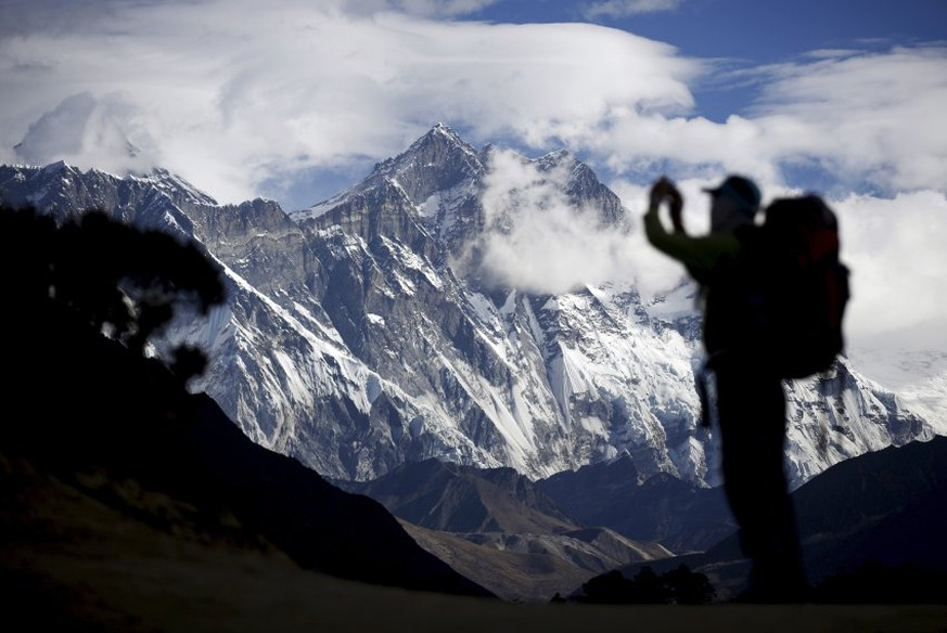 A tourist is silhouetted as he takes pictures of Mount Nuptse (C) as Mount Everest (L) is covered with clouds in Solukhumbu district, also known as the Everest region, in this picture taken November 30, 2015. To match Insight QUAKE-NEPAL/SHERPAS      REUTERS/Navesh Chitrakar  - RTX1ZEX2