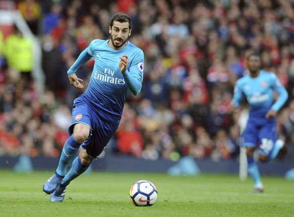 """FILE - In this Sunday, April 29, 2018 file photo, Arsenal's Henrikh Mkhitaryan runs with the ball during their English Premier League soccer match against Manchester United at the Old Trafford stadium in Manchester, England. Arsenal's Granit Xhaka and Sokratis Papastathopoulos say they want to win the Europa League title for their teammate Henrikh Mkhitaryan, who is missing the final on Wednesday, May 29, 2019 for political reasons. Xhaka says """"of course we're disappointed he's not here,"""" adding that """"we want to give him a trophy too."""" (AP Photo/Rui Vieira, file)"""