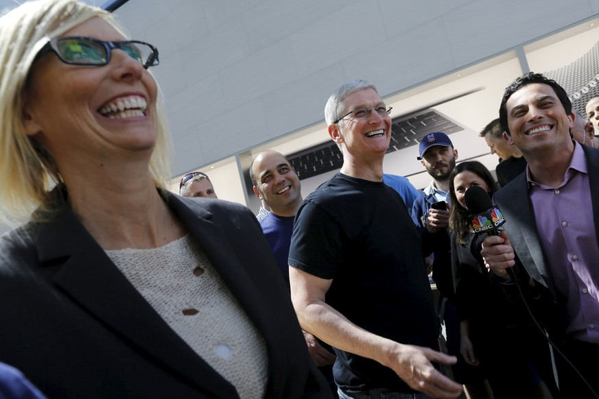 Apple CEO Tim Cook laughs during a television interview after looking over a selection of Apple Watches in Palo Alto, California April 10, 2015. Customers flocked to Apple Inc's stores around the world on Friday to get their first close-up look at the company's smartwatch, while online orders were backlogged until June. The Apple Watch, Cook's first new major product and the company's first foray into the personal luxury goods market, was available for preorder online and to try out in stores by appointment, but not to take home.  REUTERS/Robert Galbraith