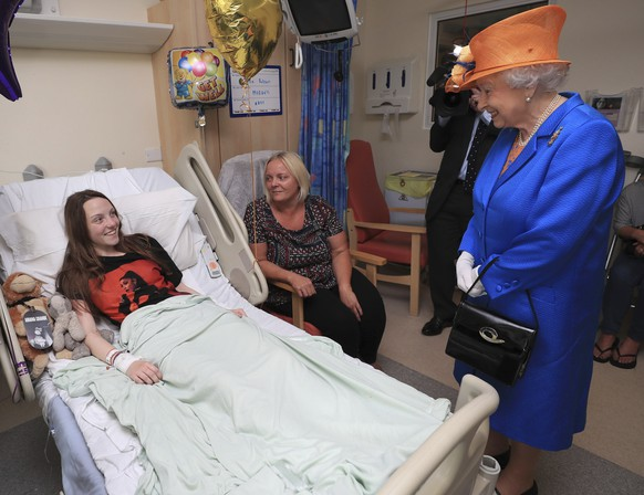 Britain's Queen Elizabeth II. right,  speaks to Millie Robson, 15,  and her mother, Marie, as she visits the Royal Manchester Children's Hospital  in Manchester England, to meet victims of the terror attack in the city earlier this week and to thank members of staff who treated them Thursday May 25, 2017. (Peter Byrne/Pool  via AP)