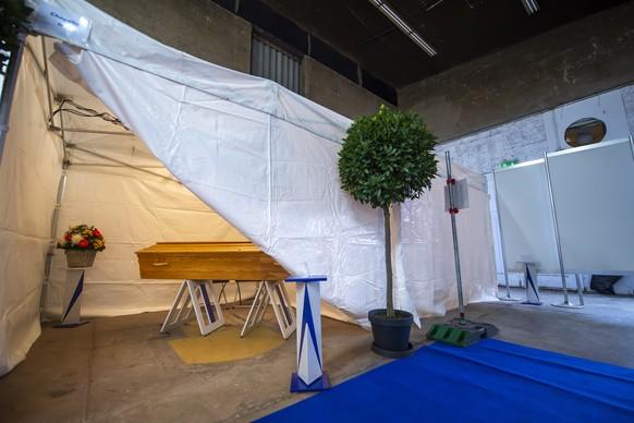 Un cercueil est photographie sous une tente qui fera office de chambre funeraire provisoire, installee dans un entrepot afin que les familles puisse ce recueillir dans l'intimite pour une ceremonie d'adieu, ce vendredi 27 novembre 2020 a Carouge pres de Geneve. Pour faire face a l'augmentation du nombre de deces due au Covid-19, des tentes provisoires ont ete dressees dans un entrepot carougeois pour accueillir des defunts. Ce dispositif, mis en place a la demande des Pompes funebres generales, permet aux familles de ne pas attendre dix jours avant de voir leur proche decede. (KEYSTONE/Martial Trezzini)
