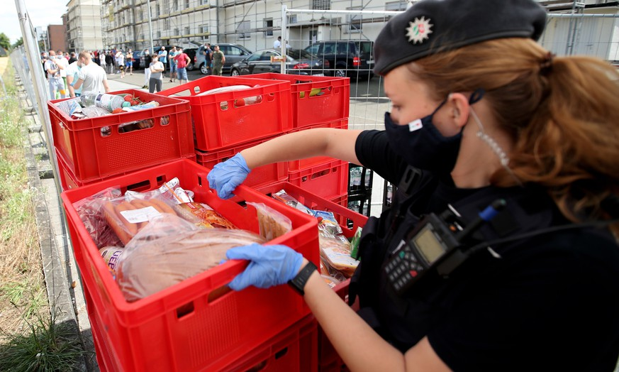 epa08502029 A policewoman helps to deliver food for quarantined employees of the meat processing company Toennies in the district Suerenheide in Verl, 22 June 2020. According to media reports, over 1300 Toennies employees at the Rheda-Wiedenbrueck plant have tested positive for the SARS-CoV-2 coronavirus that causes the pandemic COVID-19 disease.  EPA/FRIEDEMANN VOGEL