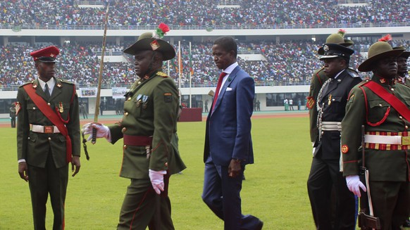 The Patriotic Front's Edgar Lungu, centre, inspects a guard of honor after being sworn in as president at an inauguration ceremony, in Lusaka Sunday, Jan. 25, 2015 after he won the president elections. Lungu the candidate from the ruling Patriotic Front, has won Zambia's presidential election called after President Michael Sata died in October, the acting chief justice announced late Saturday. (AP Photo/Moses Mwape)