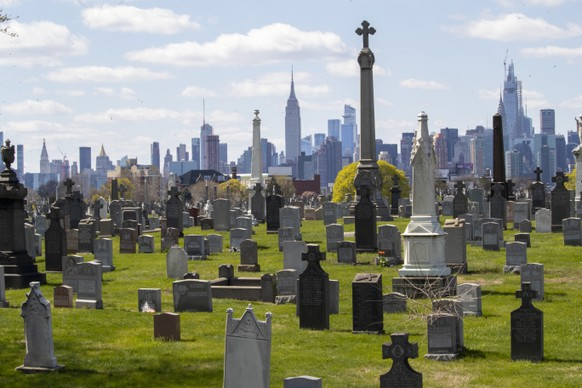 The Empire State building and the Manhattan skyline are seen behind the tombstones at Calvary Cemetery, Saturday, April 11, 2020, in the Maspeth neighborhood of the Queens borough of New York. The U.S. has recorded nearly 20,000 deaths from the coronavirus, overtaking Italy for the highest death toll in the world. Nearly half of the deaths in the United States happened in the New York state, but fear is mounting over the spread of the virus into the nation's heartland. (AP Photo/Mary Altaffer)