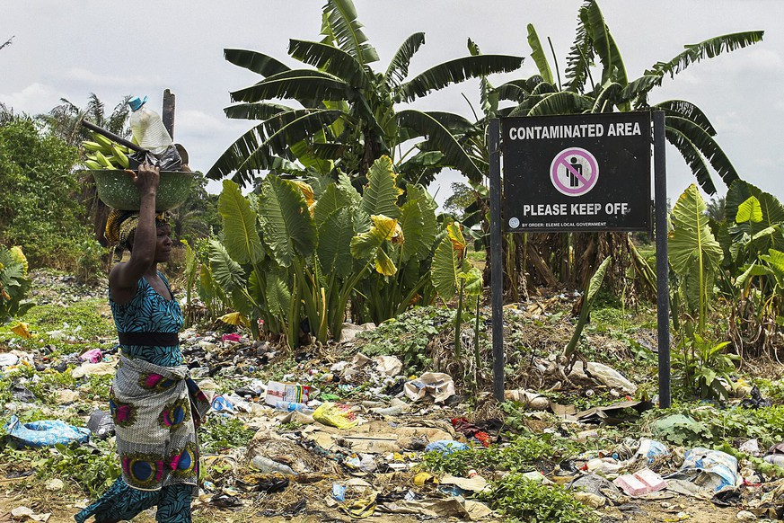 epa05203261 A Nigerian woman walks past a sign on polluted land warning of contamination in the Ogale community in the oil rich Niger Delta, Nigeria, 09 March 2016. Oil company Shell is being sued in London for the second time in five years over spills in the Niger Delta. The Ogale community of around 40,000 people in Rivers State in the Niger Delta are predominantly farmers or fishermen and are some of the claimants wanting Shell to clean up their land. Their case is being handled by law firm Leigh Day. Spills since 1989 have meant they don't have clean drinking water, farmland or rivers according to their claim. A November 2015 report by Amnesty International indicates four spill sites Shell said it planned cleaning up are still contaminated.  EPA/TIFE OWOLABI
