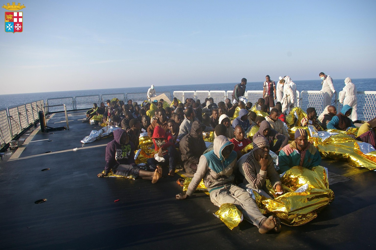 epa04163061 A handout picture provided by the Italian Navy Press Office shows North African immigrants on board a ship after being rescued off the coast of Sicily, southern Italy, 11 April 2014. The Italian navy rescued 800 North African immigrants off the coast of Libya late 10 April in the latest in a string of pick-ups off rickety boats that have been launched like flotillas during the recent spell of warm weather. The migrants were on board seven rust-buckets and large dinghies that were intercepted by four Navy frigates and a Finance Guard motorboat about 70 nautical miles south of the stepping-stone Italian island of Lampedusa, which is closer to Libya than to Sicily. Earlier this week Italy issued a fresh call for help from the European Union after rescuing more than 4,000 migrants in 48 hours.  EPA/ITALIAN NAVY PRESS OFFICE / HANDOUT  HANDOUT EDITORIAL USE ONLY/NO SALES