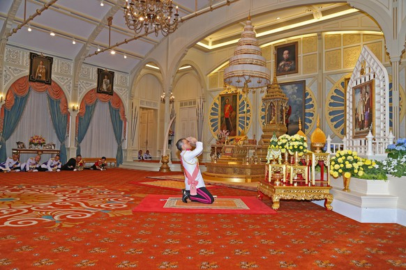 Thailand's new King Maha Vajiralongkorn Bodindradebayavarangkun pays respect to a picture of Thailand's late King Bhumibol Addlyadej and Queen Sirikit, as he accepts an invitation from parliament to succeed his father, at Bangkok's Dusit Palace in Bangkok, Thailand, December 1, 2016. Thailand Royal Household Bureau/Handout via REUTERS.  ATTENTION EDITORS - THIS IMAGE WAS PROVIDED BY A THIRD PARTY. EDITORIAL USE ONLY. NO RESALES. NO ARCHIVE.      TPX IMAGES OF THE DAY