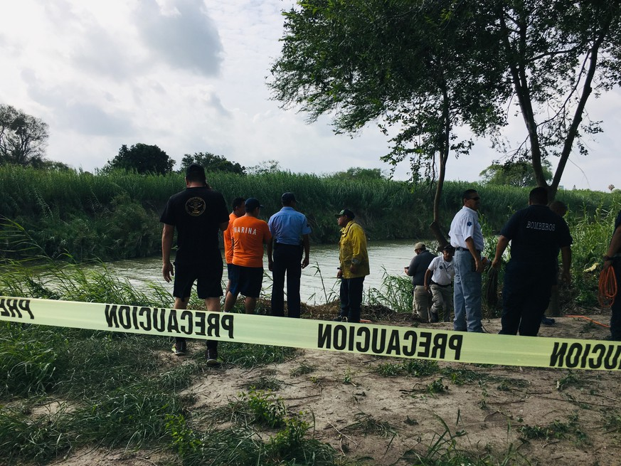 Authorities stand behind yellow warning tape along the Rio Grande bank where the bodies of Salvadoran migrant Oscar Alberto Martínez Ramírez and his nearly 2-year-old daughter Valeria were found, in Matamoros, Mexico, Monday, June 24, 2019, after they drowned trying to cross the river to Brownsville, Texas. Martinez' wife, Tania told Mexican authorities she watched her husband and child disappear in the strong current. (AP Photo/Julia Le Duc)