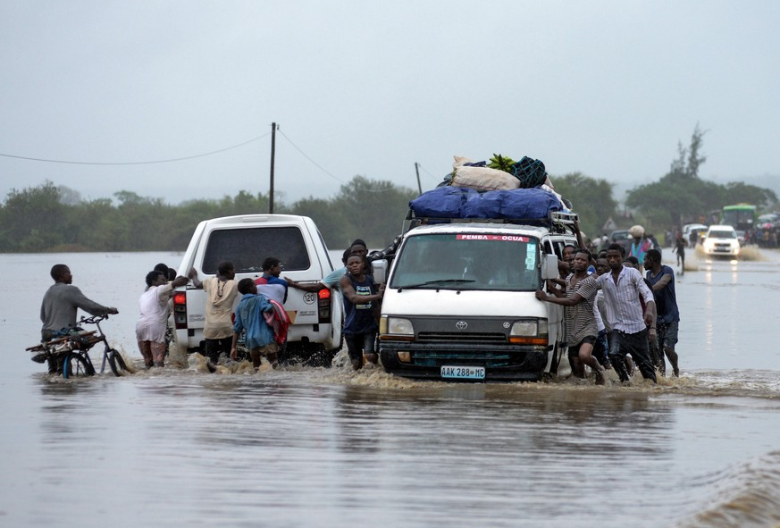 epa07538170 People push vehicles on a flooded road after the passage of Cyclone Kenneth in Metuge, Cabo Delgado, northern Mozambique, 28 April  2019 (issued 30 April 2019). The passage of Cyclone Kenneth through Cabo Delgado province in the North of the country costs 38 lives and 39 people were injured, affecting around 168,000 people in all with widespread flooding.  EPA/ANTONIO SILVA