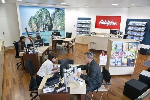 """""""Hotelplan"""" travel agent Talisa Arpino hands over a customer's travel documents, pictured on May 10, 2010 at the """"Hotelplan"""" travel agency in Zurich Oerlikon, Switzerland. (KEYSTONE/Martin Ruetschi)  Hotelplan-Mitarbeiterin Talisa Arpino uebergibt am 10. Mai 2010 im Reisebuero in Zuerich-Oerlikon einem Kunden die Reiseunterlagen. (KEYSTONE/Martin Ruetschi)"""