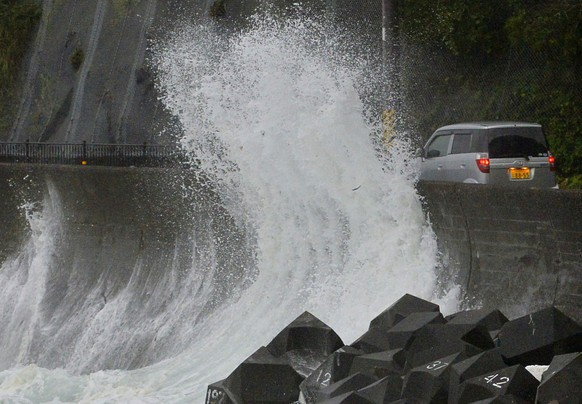 A big sea wave hit against a concrete wall to a road in Kushimoto, western Japan, Saturday, Aug. 9, 2014. Typhoon Halong is lashing Japan as it enters a holiday week, injuring six people and causing authorities to order the evacuation of half a million people near swollen rivers. Japan's Meteorological Agency issued a special warning for heavy rain in Mie prefecture in central Japan, prompting two towns to order about 500,000 residents to evacuate due to a fear of flooding from swollen rivers. The agency said heavy rain in the area would continue overnight. (AP Photo/Kyodo News) JAPAN OUT