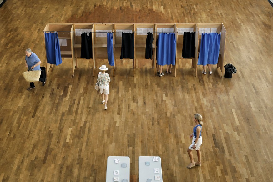 People walk in a polling station before casting their ballots in the first round of parliamentary elections, in Lyon, central France, Sunday, June 11, 2017. French voters are choosing lawmakers in the lower house of parliament in a vote that is crucial for newly-elected president Emmanuel Macron. (AP Photo/Laurent Cipriani)