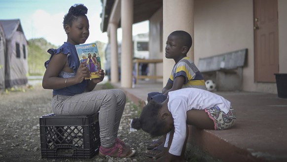 In this March 2, 2020 photo, Keline pretends to be a teacher to kids living in a tent camp based ch in Marsh, Harbour, Bahamas. The tents serve as a temporary housing solution following Hurricane Dorian ravaging the Bahamas in September. (Mackenzie Behm/Fresh Take Florida via AP)
