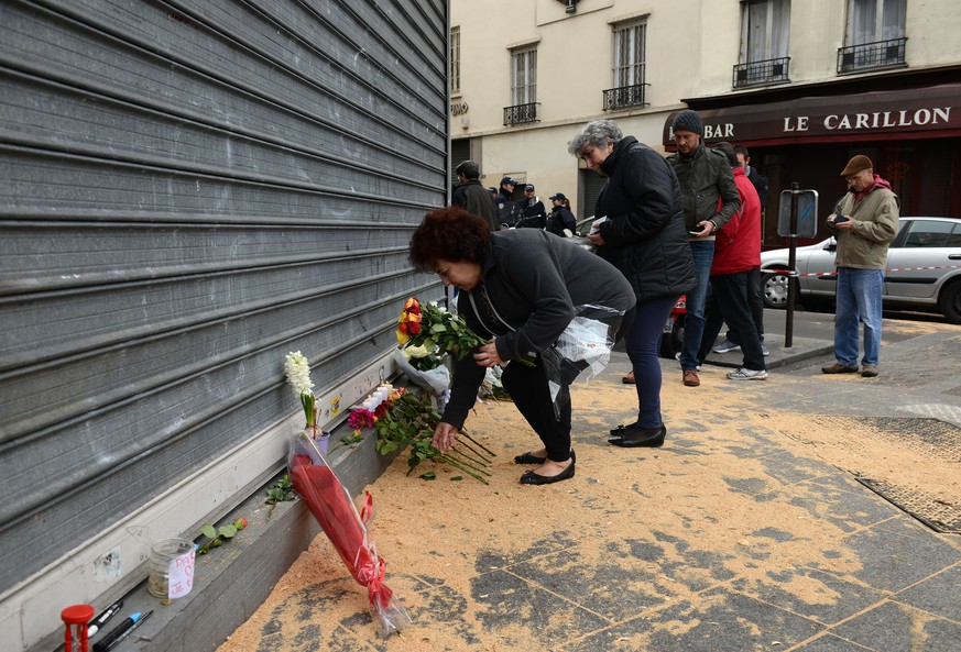 PARIS, FRANCE - NOVEMBER 14:  A woman places Flowers outside Le Petit Cambodge restaurant, the day after a deadly attack on November 14, 2015 in Paris, France. At least 120 people have been killed and over 200 injured, 80 of which seriously, following a series of terrorist attacks in the French capital.  (Photo by Antoine Antoniol/Getty Images)