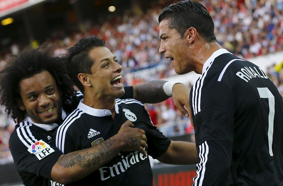 Real Madrid's Cristiano Ronaldo (R) celebrates in front of Marcelo (L) and Javier Hernandez
