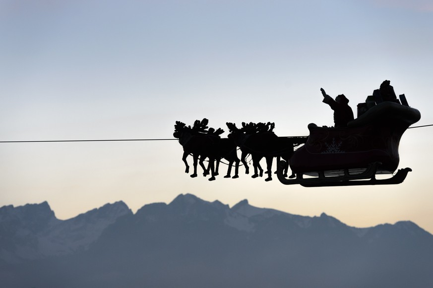 Santa Claus waves to the crowd from his flying sleigh drawn by reindeer over the Geneva Lake and in front of the Swiss and French alps as the sunset on the first day of the 20th edition of the Christmas Market in Montreux, Switzerland, Friday, November 21, 2014. Santa Claus is
