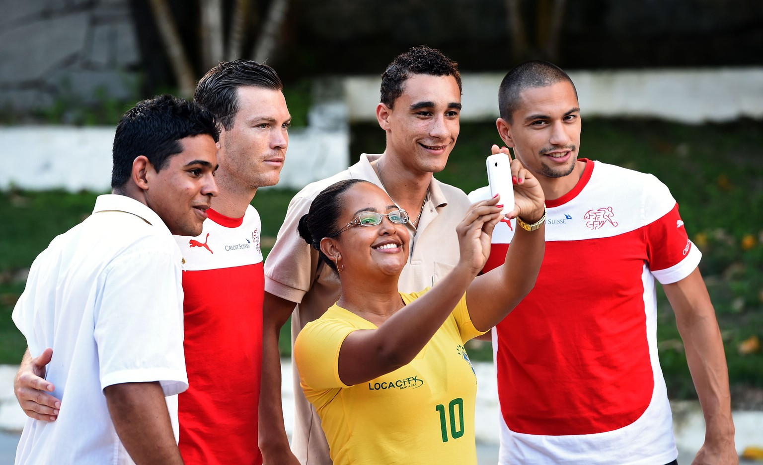 Switzerland's midfielder and captain Goekhan Inler (R) and Switzerland's defender Stephan Lichtsteiner (2ndL) pose with football fans after a press conference at the Praia Hotel in Porto Seguro on June 10, 2014, ahead of the 2014 FIFA World Cup football tournament in Brazil.   AFP PHOTO/ ANNE-CHRISTINE POUJOULAT