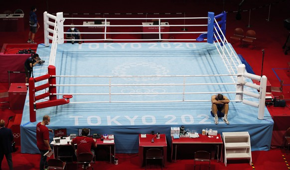 epa09384001 Mourad Aliev of France sits outside the ring in protest after losing his match against Frazer Clarke of Great Britain in the Men's Super Heavy (+91kg) quarterfinal match of the Boxing events of the Tokyo 2020 Olympic Games at the Ryogoku Kokugikan Arena in Tokyo, Japan, 01 August 2021.  EPA/RUNGROJ YONGRIT