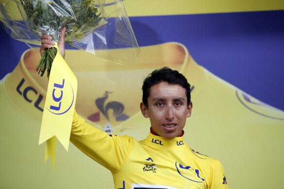 New overall leader Colombia's Egan Arley Bernal Gomez wearing the yellow jersey celebrates on the podium after the nineteenth stage of the Tour de France cycling race with start in Saint Jean De Maurienne, France, Friday, July 26, 2019. Tour de France organizers stopped Stage 19 of the race because of a hail storm as Julien Alaphilippe lost his yellow jersey to Egan Bernal. (AP Photo/Christophe Ena)