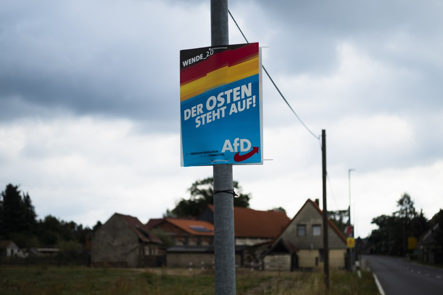 In this Friday, Aug. 16, 2019 photo an election campaign poster of German Alternative for Germany, AfD, party for the Saxony state election reading: 'ÄöThe East stands up' is displayed in the village Gruenwald near Bautzen, Germany. Two elections in eastern Germany's states Brandenburg and Saxony on Sept. 1, 2019 look set to bring big gains for the far-right Alternative for Germany party and another blow to the traditional parties that form the national government. (AP Photo/Markus Schreiber)