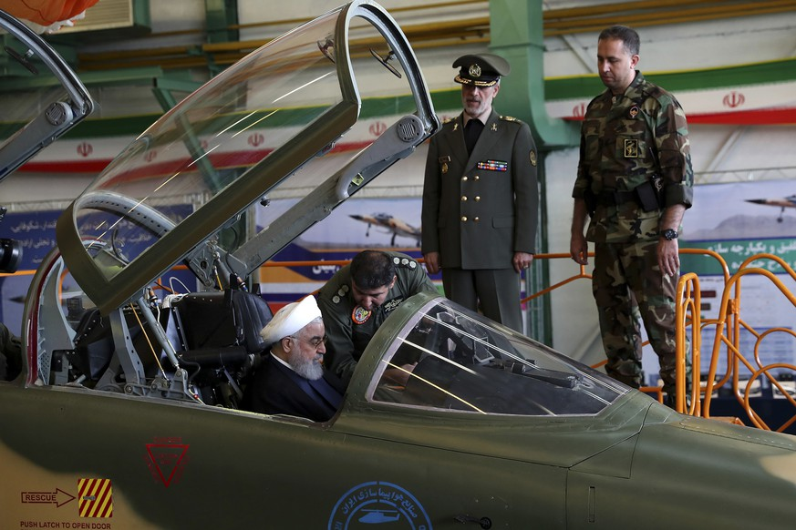 In this photo released by official website of the office of the Iranian Presidency, President Hassan Rouhani is briefed by an air force pilot as he sits in the cockpit of a fighter jet, before an inauguration ceremony of the aircraft, Iran, Tuesday, Aug. 21, 2018. Iran on Tuesday displayed a new twin-seat fighter jet it says is all Iranian-made and which allegedly has advanced avionics and fire control systems. Defense Minister Gen. Amir Hatami stands at second right. (Iranian Presidency Office via AP)