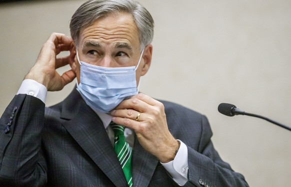 FILE - In this June 16, 2020, file photo, Texas Gov. Greg Abbott adjusts his mask after speaking in Austin, Texas.  Abbott on Thursday, July 2, ordered that face coverings must be worn in public across most of the state, a dramatic ramp up of the Republican's efforts to control spiking numbers of confirmed coronavirus cases and hospitalizations. (Ricardo B. Brazziell/Austin American-Statesman via AP, File) Greg Abbott