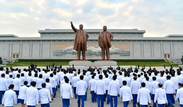 epa04433998 A picture released by the North Korean Central News Agency (KCNA) on 06 October 2014 shows North Korea's Asian Games athletes pay tribute at the base of statues of the late leaders Kim Il-sung and Kim Jong-il at Mansudae Hill in Pyongyang, North Korea, 05 October 2014.  EPA/KCNA SOUTH KOREA OUT  NO SALES