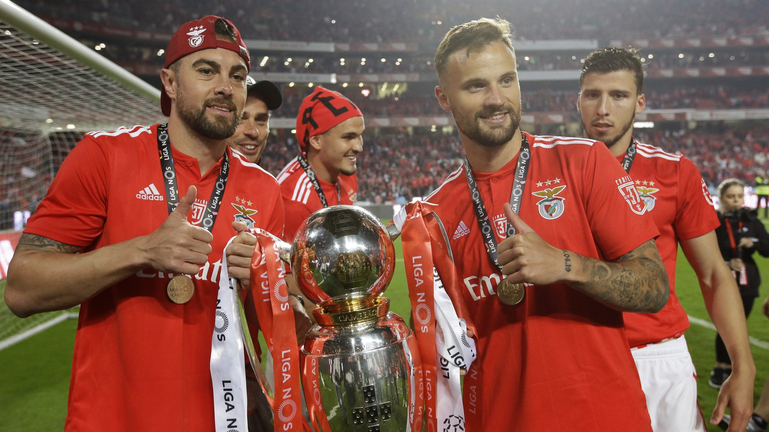 Benfica's team captain Jardel, left, and Haris Seferovic pose with the trophy after the Portuguese league last round soccer match between Benfica and Santa Clara at the Luz stadium in Lisbon, Saturday, May 18, 2019. Benfica won 4-1 to clinch the championship title. (AP Photo/Armando Franca)