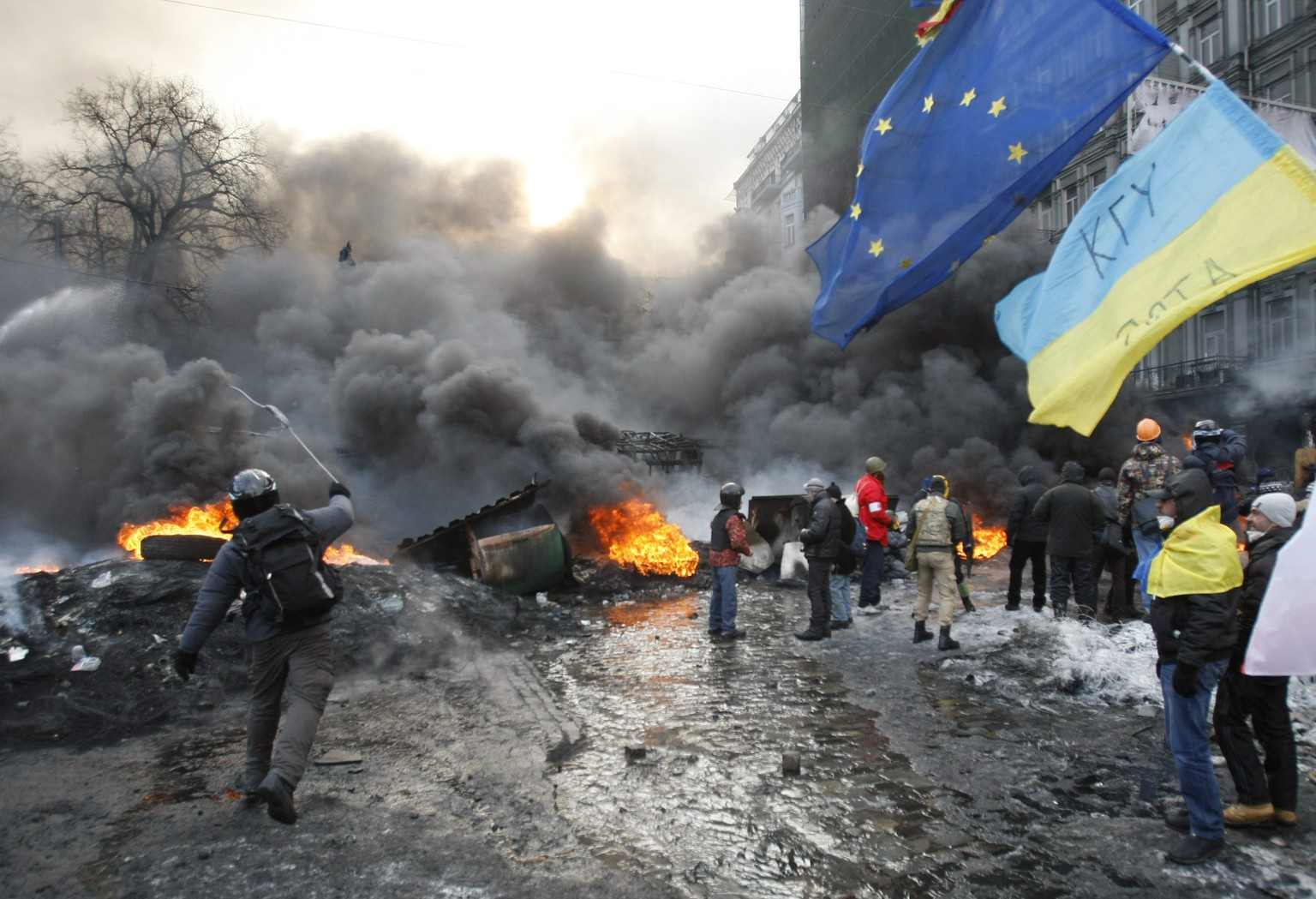A protester throws stone during clashes, in central Kiev, Ukraine, Thursday Jan. 23, 2014. Thick black smoke from burning tires engulfed parts of downtown Kiev as an ultimatum issued by the opposition to the president to call early election or face street rage was set to expire with no sign of a compromise on Thursday. (AP Photo/Darko Vojinovic)