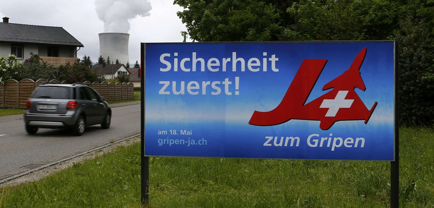 A car drives past a poster to support the purchase of Gripen fighter jets next to the nuclear power plant in Leibstadt May 1, 2014. Switzerland will vote May 18 in a referendum on the purchase of 22 Gripen fighter jets from Swedish defence firm Saab. The text on the poster reads