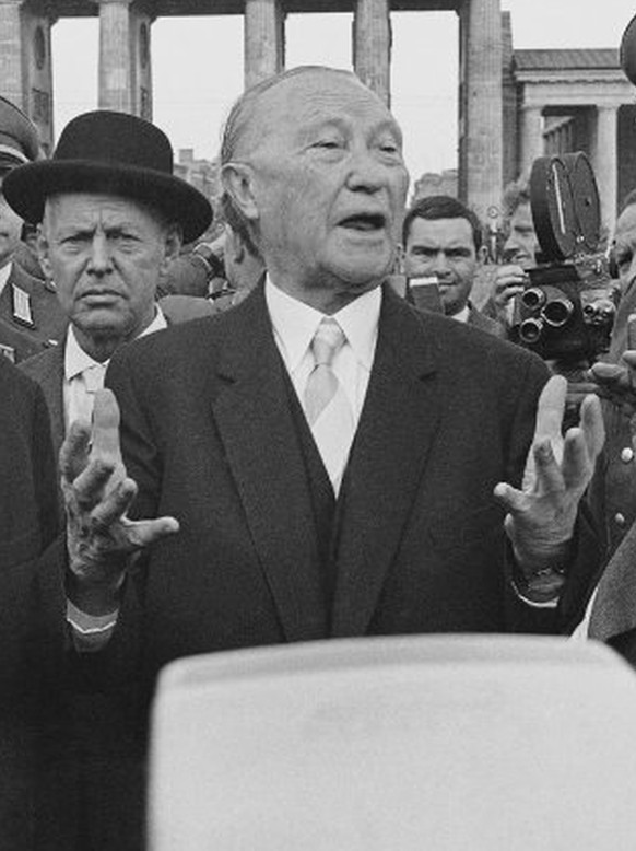 Konrad Adenauer, West German Chancellor, gestures with hands while talking to Ernst Lemmer, right, minister for all-German Affairs. At left, during the Chancellor's tour of West Berlin  August 22, 1961, is the city's Deputy Mayor Fritz Amrehn. Brandenburg gate on border between East and West Berlin, is in background. (AP Photo)