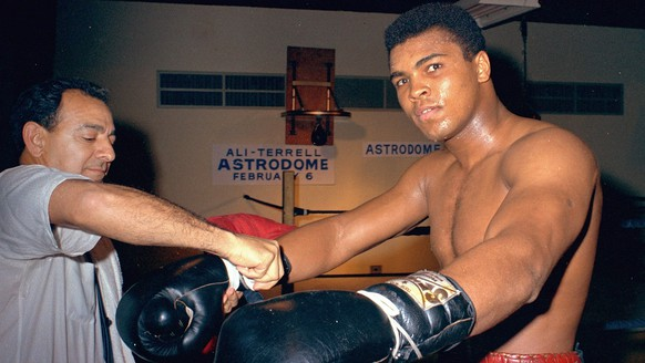 FILE - In this February 1967, file photo, Muhammad Ali gets his gloves laced by trainer Angelo Dundee while training in Houston, Texas, for a title fight against Ernie Terrell. Ali never spent a day in prison for his actions even though he was sentenced to serve five years for draft evasion before the Supreme Court overturned his case on a technicality. But many black athletes have paid when taking a stand, or a knee,  for speaking out for social or political change. Ali lost the heavyweight title and spent three years in forced exile from the ring. (AP Photo)/File)