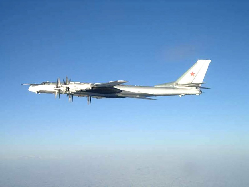 FILE - In this Feb. 9, 2008 file photo released by the U.S. Navy, one of two Russian Tupolev 95 Bear long rang bomber aircraft is seen near the U.S. Navy aircraft carrier USS Nimitz, south of Japan. Russia's defense minister says the military will conduct regular long-range bomber patrols, ranging from the Arctic Ocean to the Caribbean and the Gulf of Mexico.  (AP Photo/U.S. Navy)