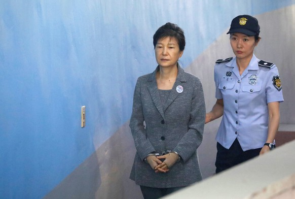 epa08936551 (FILE) - Former South Korean President Park Geun-hye (L) is escorted to a courtroom  to stand trial on alleged bribery, abuse of power and leaks of government secrets, in Seoul, South Korea, 25 August 2017 (reissued 14 January 2021). South korea's Supreme Court on 14 January upheld the 20-year prison term for former president Park Geun-hye, who was impeached and ousted in 2017 following a corruption scandal.  EPA/KIM HONG-JI / POOL