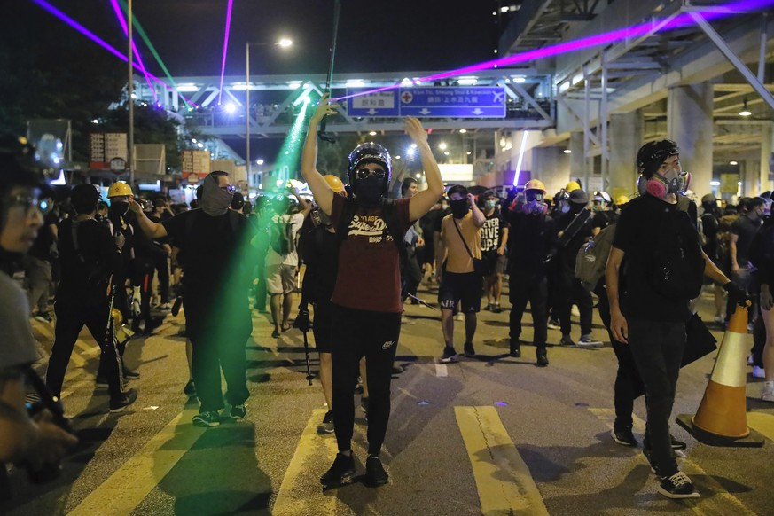 Demonstrators shine laser pointers outside the Yuen Long MTR station during a protest in Hong Kong, Wednesday, Aug. 21, 2019. Hong Kong riot police faced off briefly with protesters occupying a suburban train station Wednesday evening following a commemoration of a violent attack there by masked assailants on supporters of the anti-government movement. (AP Photo/Kin Cheung)