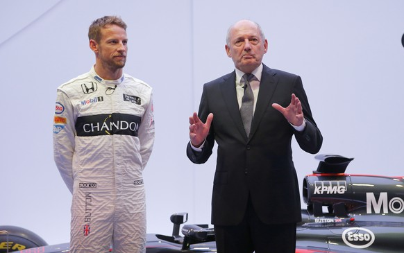 McLaren F1 car brand CEO Ron Dennis, right, gestures with  Britain's McLaren F1 driver Jenson Button at left, during a presentation  in Woking, England, Wednesday, Sept. 30, 2015. McLaren announced a new sponsorship deal with champagne brand Chandon.  (AP Photo/Frank Augstein)