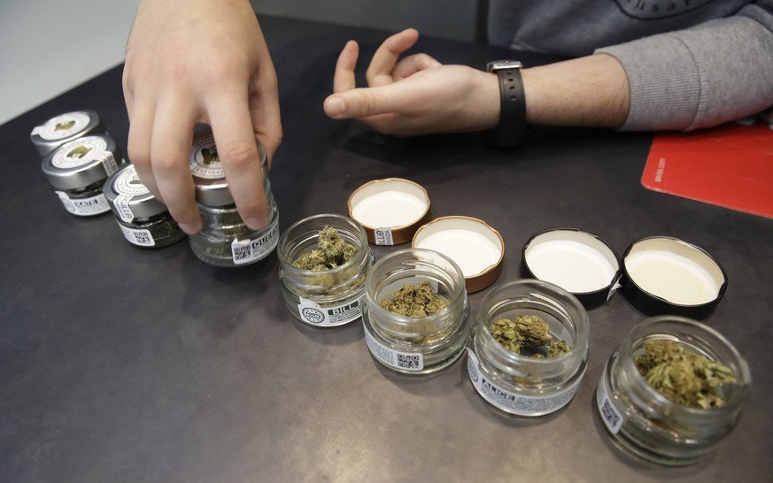 In this  Thursday, June 6, 2019 a shop assistant opens jars of cannabis buds at a cannabis light store in Milan, Italy. Interior Minister Matteo Salvini has been an outspoken opponent of the marijuana light businesses that sprouted up around the country after pioneering 2016 legislation that many saw as a step toward eventual marijuana liberalization.(AP Photo/Luca Bruno)
