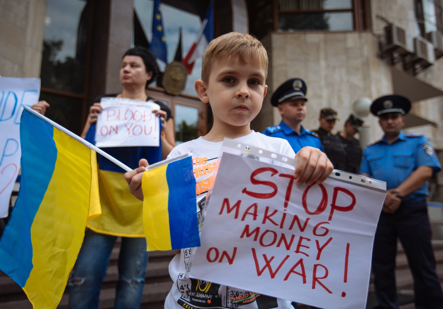 epa04326400 A young boy holds a sign and Ukrainian national flag during a rally in front of the French embassy in Kiev over the possible sale of two Mistral helicopter carriers to Russia by France, in Kiev, Ukraine, 22 July 2014. According to various media reports, France, which signed a deal with Russia in 2011 on the sale of the ships, has been urged to sell the warships to NATO instead, in light of the ongoing crisis gripping Ukraine.  EPA/ROMAN PILIPEY