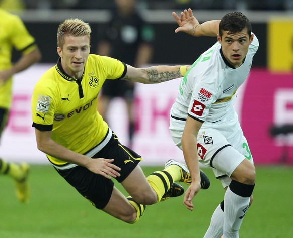 Dortmund's Marco Reus, left, and Moenchengladbach's Granit Xhaka of Switzerland challenge for the ball during the German first division Bundesliga soccer match between Borussia Dortmund and Borussia Moenchengladbach in Dortmund, Germany, Saturday, Sept. 29, 2012. (AP Photo/Michael Probst)