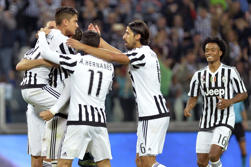 Juventus' Paulo Dybala, left, celebrates with his teammates after scoring during a Serie A soccer match between Juventus and Bologna at the Juventus stadium, in Turin, Italy, Sunday, Oct. 4, 2015. (AP Photo/Massimo Pinca)