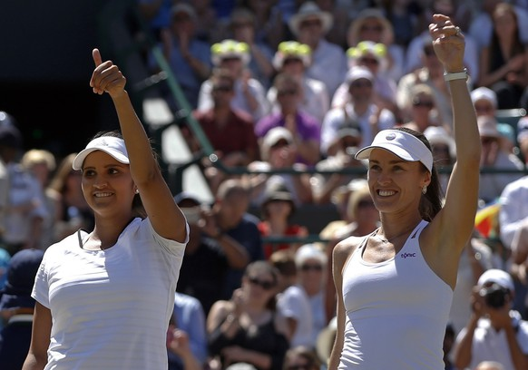 Martina Hingis of Switzerland, right celebrates with partner Sania Mirza of India as they win their women's semifinal doubles match against Raquel Kops-Jones of the United States and Abigail Spears of the United States, at the All England Lawn Tennis Championships in Wimbledon, London, Friday, July 10, 2015. Hingis and Mirza won the match 6-1, 6-2. (AP Photo/Alastair Grant)