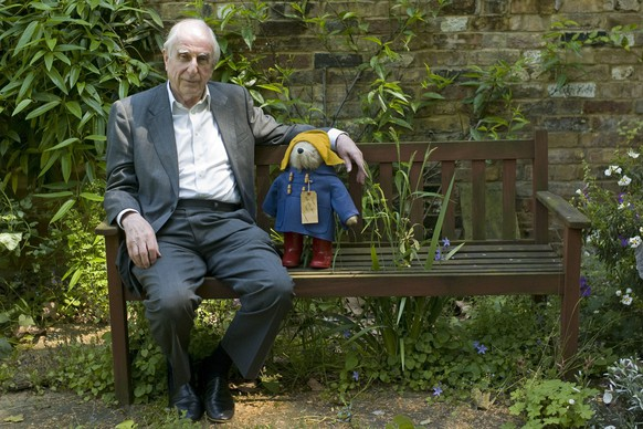 FILE - In this Thursday, June 5, 2008 file photo, British author Michael Bond sits with a Paddington Bear toy during an interview with The Associated Press in London. Publisher HarperCollins says Michael Bond, creator of globe-trotting teddy Paddington bear, died on Tuesday June 27, 2017, aged 91. (AP Photo/Sang Tan, File)