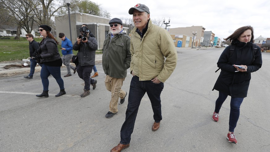 2020 Democratic presidential candidate Washington Gov. Jay Inslee, center, tours flood damage, Friday, April 12, 2019, in Hamburg, Iowa. (AP Photo/Charlie Neibergall)