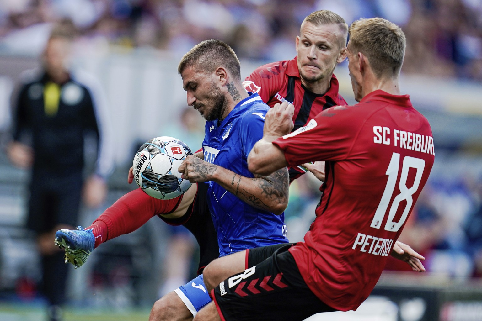 From left, Hoffenheim's Konstantinos Stafylidis challenges for the ball with Freiburg's Jonathan Schmid and Nils Petersen during the German Bundesliga soccer match between TSG 1899 Hoffenheim and SC Freiburg in Sinsheim, Germany, Sunday, Sept, 15, 2019. (Uwe Anspach/dpa via AP)