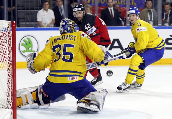 Sweden goalie Henrik Lundqvist makes a save in front of Canada's Chris Lee, center, during the Ice Hockey World Championships final match between Canada and Sweden in the LANXESS arena in Cologne, Germany, Sunday, May 21, 2017. (AP Photo/Petr David Josek)